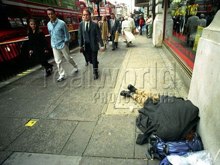 Londoners pass a homeless man on Oxford street, Central London, UK.
