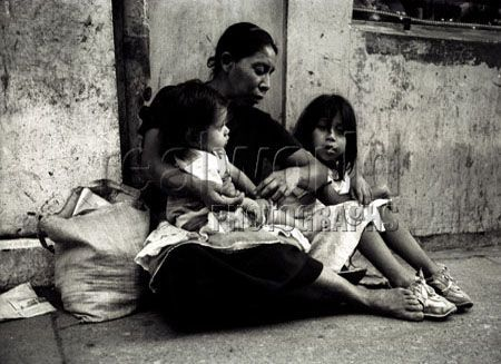A young family sit begging on a street in Guatemala City, Guatemala, Central America.