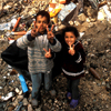 Two Palestinian children flash smiles and victory signs amid the destruction around them in Jenin refugee camp in 2002. The Israel Defense Forces bulldozed the center after a fierce fight with militants.