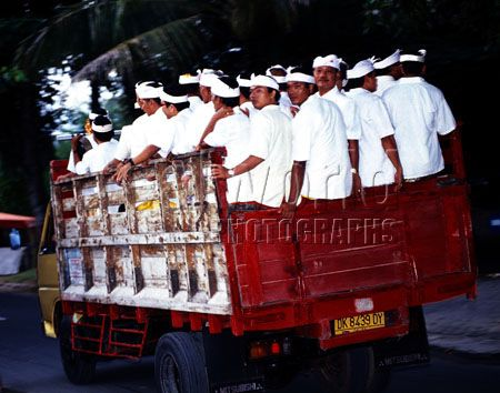 Balinese men crammed into a truck race by on their way to a temple for religious festivities in Tejung Benoa, Bali, Indonesia.