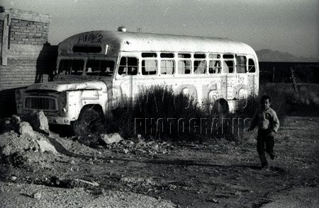 A young Mexican boy runs past an abandoned school bus in Chihuahua, Mexico.