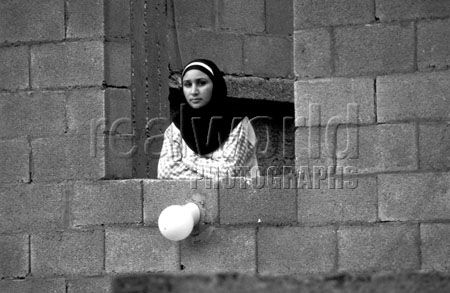 A Palestinian woman looks out from an open concrete window in the Jenin refugee camp. Palestine.