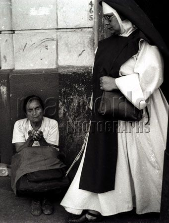 A nun ignores a woman begging for change on a street in San Salvador, El Salvador, Central America.