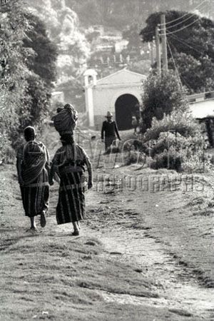 Two women dressed in traditional Guatemalan clothing is closely watched by a man at the end of this trail in Huehuetenango, Guatemala, Central America.