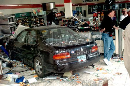 711 employees wait for a tow truck to arrive after a woman lost control and smashed her car into the store window in Vancouver, British Columbia, Canada.